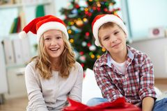 Merriment. Portrait of happy siblings looking at camera on Christmas evening Royalty Free Stock Photography