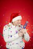 Merriment. Portrait of joyful man in Santa cap and white pullover having fun with confetti cracker Stock Photo