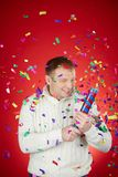 Merriment. Portrait of joyful man in white pullover having fun with confetti cracker Royalty Free Stock Images