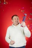 Merriment. Portrait of joyful man in white pullover having fun with confetti cracker Stock Photography