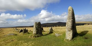 Merrivale stone row on dartmoor. Ancient stone row at Merrivale on Dartmoor with bright sunshine and cloudy blue sky royalty free stock image