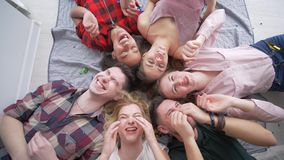 Merry beautiful friends blowing bubble gum lying on back together and smile at camera during a home party, top view. Merry beautiful friends blowing bubble gum stock footage