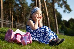 Merry beautiful girl sitting on green grass Stock Images