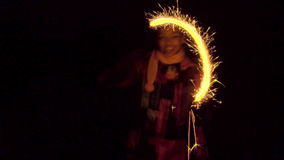 Merry black girl drawing lines in the air with sparkler. In the night stock video footage