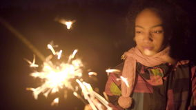 Merry black girl drawing lines in the air with sparkler. In the night stock video