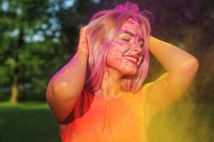 Merry blonde girl having fun with colorful dry paint at the park. Concept for festival Holi. Merry blonde woman having fun with colorful dry paint at the park stock photo