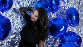 Merry brunette with evening make-up among bright inflatable balloons at event. Merry brunette with evening make-up among bright inflatable balloons on background stock video footage