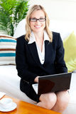 Merry businesswoman with glasses using her laptop Royalty Free Stock Photos