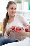 Merry caucasian woman giving a present to her surprised friend f Stock Photography