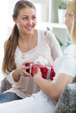 Merry caucasian woman giving a present to her surprised friend f Royalty Free Stock Image