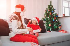 Merry Christmas and Happy New Year. Picture of happy kid sitting on sofa and hold white small round sweet. She looks at stock photos