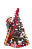 Merry christmas. Boy ready to place the star on the top of the tree Stock Photos