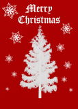 Merry Christmas. A cheerful red christmas message with snowy Christmas tree and snowflakes over red background Royalty Free Stock Photo