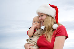 Merry Christmas. Young attractive mom with Santa's hat and the little baby on the cloudy sky background Stock Image