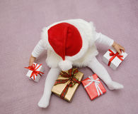 Merry Christmas!. The small beautiful child sits on a floor among Christmas gifts Stock Images