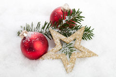 Merry Christmas. Christmas baubles, Stars and a branch in a landscape of snow - studio shot Royalty Free Stock Image