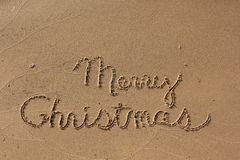 Merry Christmas. Written in wet sand on the beach Stock Photography