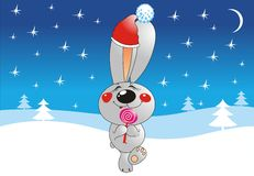 Merry Christmas. Rabbit looks like Santa Claus and winter landscape on the background Royalty Free Stock Images