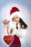 Merry Christmas. Studio portrait of sweet little girl with red hearth stock images