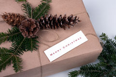 Merry Christmas. This image features a package wrapped in old-fashioned brown paper and twine, topped with pine branches and pine cones. A card wishing Merry Royalty Free Stock Photo