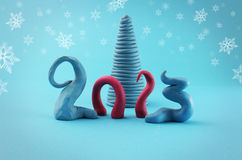 Merry christmas 2013. Logo 2013 with plasticine, trees and cyan background stock illustration