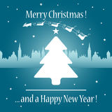 Merry Christmas. Abstract blue background with white Christmas tree in front of a town and Santa's sledges pulled by reindeer flying over the town Royalty Free Stock Photo
