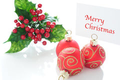 Merry Christmas. Three red Christmas ball ornament with gold and with green twig, a postcard with the caption Merry Christmas on a white background Stock Photography