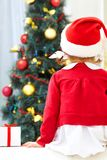 Merry Christmas. Little girl sitting against Christmas tree. Back view Royalty Free Stock Photography