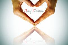 Merry christmas. Hands forming a heart and the sentence merry christmas Stock Photo
