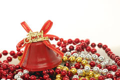 Merry Christmas. Red Merry Christmas bell on beads Stock Photo