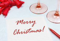 Merry Christmas. Written on paper with a festive setting of ribbons and wine glasses Stock Photo