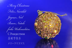 Merry christmas. A golden christmas ball on a blue background and the sentence merry christmas written in english, spanish, french, italian, german, russian Royalty Free Stock Images