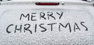 Merry Christmas. In snow on back window of car Royalty Free Stock Photo