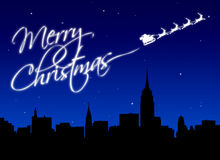 Merry Christmas. Santa writing merry christmas in glitters with his sled over the New York skyline Stock Photos