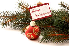 Merry Christmas. Christmas ornament with message Merry Christmas before fir branch on white background Stock Photo