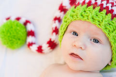 Merry Christmas Baby!. Baby wearing red white and green striped knit hat Stock Photo