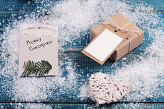 Merry Christmas background. Christmas vintage gift box with with copy space blank tag on snow and blue background. Stock Photos