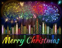 Merry Christmas banner decorated with fireworks exploding in night sky over downtown city Royalty Free Stock Image