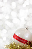 Merry Christmas Bauble. White Christmas bauble with Merry Christmas sign and light reflections on background of defocused  lights Stock Images