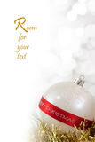 Merry Christmas Bauble. White Christmas bauble with Merry Christmas sign and light reflections on background of defocused  lights Royalty Free Stock Images