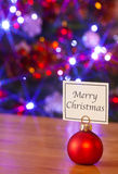 Merry Christmas bauble and tree. A red bauble placeholder with a card saying Merry Christmas, fairy lights blurred on the Christmas tree behind Stock Images