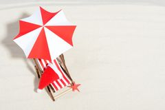 Merry Christmas on beach concept. Lounge chair with umbrella and Santa hat royalty free stock image