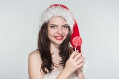 Merry Christmas. Beautiful young woman in a red Mrs. Claus costume and Santa cap with candy. On a white background stock photo