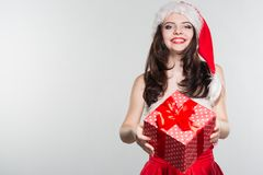 Merry Christmas. Beautiful young woman in a red Mrs. Claus costume and Santa cap holding gift box. On a white background royalty free stock photo