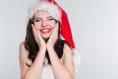 Merry Christmas. Beautiful young woman in a red Mrs. Claus costume and Santa cap holding hands near the face on her cheeks. On a white background royalty free stock image