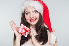 Merry Christmas. Beautiful young woman in a red Mrs. Claus costume and Santa cap holding gift box. On a white background stock photography