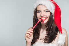 Merry Christmas. Beautiful young woman in a red Mrs. Claus costume and Santa cap with candy. On a white background royalty free stock image