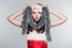 Merry Christmas. Beautiful young woman in a red Mrs. Claus costume and Santa cap with decoration. On a white background stock photography