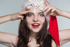Merry Christmas. Beautiful young woman in a red Mrs. Claus costume and Santa cap with snowflake. On a white background stock image