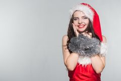 Merry Christmas. Beautiful young woman in a red Mrs. Claus costume and Santa cap with decoration. On a white background stock images